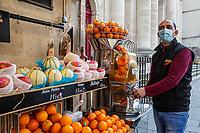 fruttivendolo con maschera di protezione  prepara una spremuta di arance vegetable shop owner  with protective mask prepare an orange juice