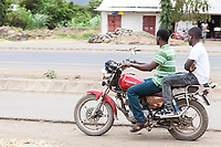 Tanzania, Mto wa Mbu Street Scene, Young Men on Motorbike, in Casual Clothing.