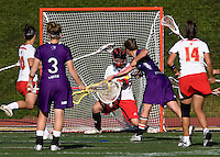 Brittany Dipper (43) of Maryland saves the shot of Erin Fitzgerald (7) of Northwestern during the NCAA Championship held in Johnny Unitas Stadium at Towson University in Towson, MD.  Maryland defeated Northwestern, 13-11, to win the title.