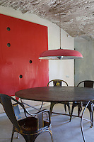 An industrial metal suspension lamp hangs above a bare metal circular table in a dining room with a textured stone and rush ceiling. The room is dominated by a contemporary painting by Catalan artist Miquel Mont.