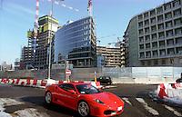 milano, una ferrari passa davanti al cantiere per il grattacielo nuova sede della regione lombardia --- milan, a ferrari passes by the construction site of the new skyscraper headquarter of Lombardy Region authority