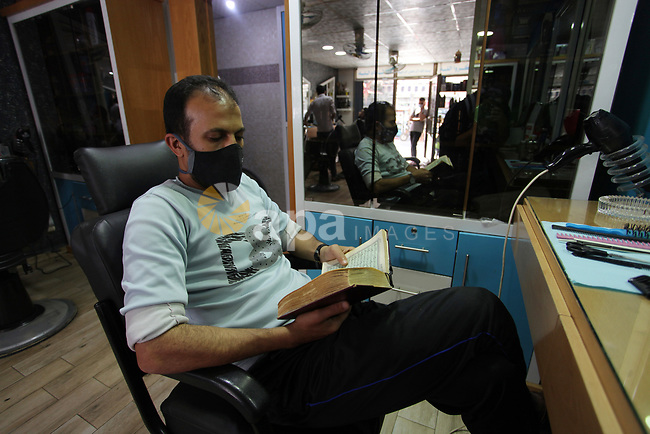 A Palestinian Muslim reads holy Quran during the Muslim holy month of Ramadan, in Gaza city, on May 01. 2021. Youth (19- 29 years) are the most group suffering from unemployment. Thus, the unemployment rate among youth reached about 39%; 24% in the West Bank and 67% in Gaza Strip. Moreover, the youth graduates of those who hold a scientific qualification of an intermediate diploma or higher are the most group suffering from unemployment, as this rate reached about 54%; (36% in the West Bank and 79% in Gaza Strip). Photo by Mahmoud Ajjour
