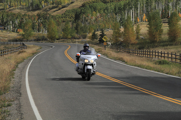Man riding motorcycle on a paved road in autumn, San Juan Mountains, Colorado.