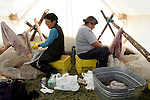 Vuntut Gwitchin First Nation women, Mary Jane Moses and Jane Montgomery, scrape caribou skins in a tent in Old Crow, Yukon Territory, Canada.