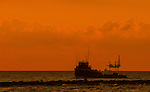 A shrimp boat passes in front off an oil rig