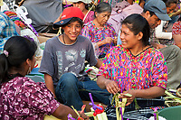 Antigua, Guatemala.  Kachiquel (Kaqchikel) WomanWearing Traditional Blouse (Guipile) and Young Boy Making Decorations for Palm Sunday.