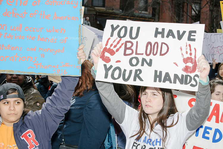 """People take part in the March For Our Lives protest, walking from Roxbury Crossing to Boston Common, in Boston, Massachusetts, USA, on Sat., March 24, 2018, in response to recent school gun violence. Here, a woman holds a sign reading """"You have blood on your hands."""""""