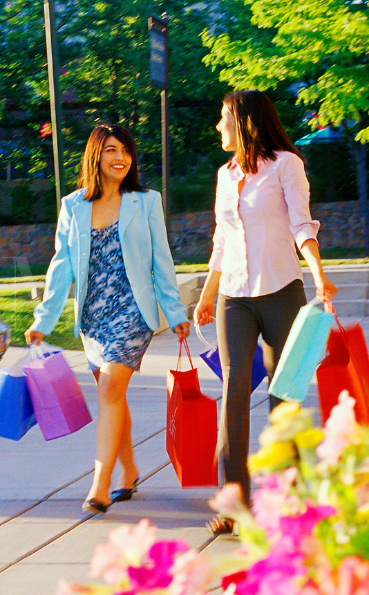 Two females at an outdoor mall shopping and carrying brightly colored shopping bags.