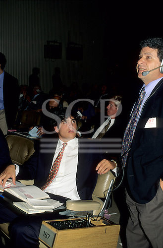 Buenos Aires, Argentina. Stock Exchange; Latin looking man with headset and man sitting with notebooks.