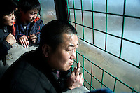Visitors to the Siberian Tiger Park in Haerbin, Heilongjiang, China, ride a tourbus through a tiger enclosure to catch a glimpse of the endangered animal.  The Siberian Tiger Park is described as a preserve to protect Siberian tigers from extinction through captive breeding.  Visitors to the park can purchase live chickens and other meat to throw to the tigers.  The Siberian tiger is also known as the Manchurian tiger.