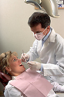 A dentist prepares to check a woman patient's teeth.