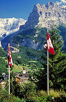The Swiss Alps, Grindelwald, Switzerland. alpine landscape, mountains, geography, Swiss flags, village nestled in a valley. Grindelwald, Switzerland.
