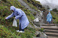 Tourists picking flowers near the Hailuogou glacier in western Sichuan Province, China. As a result of rising temperatures on the Tibetan Plateau, the Hailuogou glacier has retreated over 2 km during the 20th century alone. Since the Little Ice Age, studies have revealed that the total monsoonal glacier coverage in the southeast of the Tibetan Plateau has decreased by as much as 30 percent, causing alarm in scientific circles.