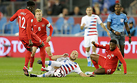 TORONTO, ON - OCTOBER 15: Michael Bradley #4 of the United States slide tackles Alphonso Davies #12 of Canada during a game between Canada and USMNT at BMO Field on October 15, 2019 in Toronto, Canada.