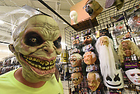 Scary is in the eyes of the trick-or-treat bag holder. David Henderson, a manager at Halloween Express at Frisco Station Mall in Rogers, models on Wednesday Oct. 6 2021 one of the ghoulish masks at the store. Go to nwaonlinecom/211010Daily/ to see more photos.<br />(NWA Democrat-Gazette/Flip Putthoff)