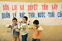 """Vietnam. Ha Tay province. Lai Xa. Three young boys smile, laugh and show their arms' muscles. On the wall, a painted slogan is writen in vietnamese language. """" The local government and the Lai Xa community have sucessfully built the progress on sanitation of solid-waste and waste-water """".  Through the construction of a main drainage and the building of sewerage as a combined system, collecting both rainwater and domestic waste water, the implementation of a flexible decentralized community sanitation project in a context of low infrastructure investment and in a peri-urban case study, such as Lai Xa, is a major sucesss. It offers importants benefits as an alternative to centralized systems, namely in terms of health improvements and by the possibility of dealing with wastewater locally, through households and decentralized municipal structures. Lai Xa is a typical hamlet (village) of the Red River delta region and is part of the Kim Chung commune located 15 km west of Hanoi. This peri-urban location is under increasing pressure from the forces of urbanization. 06.04.09  © 2009 Didier Ruef"""