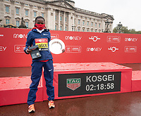 4th October 2020, London, England; 2020 London Marathon; Brigid Kosgei (KEN) with the clock showing her marathon time outside Buckingham Palace with her trophy after winning the Elite Women's Race at the historic elite-only Virgin Money London Marathon taking place on a closed-loop circuit around St James's Park in central London on Sunday 4 October 2020.