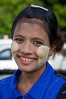 Myanmar, Burma, Yangon.  Burmese Woman with Thanaka Paste on Face as a Cosmetic Sunscreen.