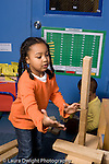 Educaton preschool 4-5 year olds block area girl holding out hands in case wood blocks she just put on construction fall down hair in braids vertical