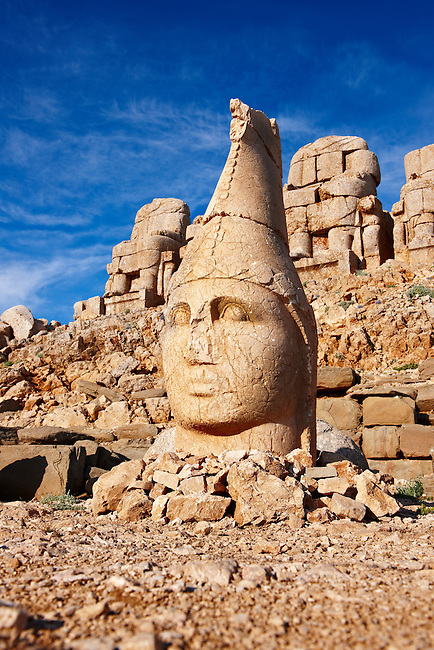 Picture & photo of the statues of around the tomb of Commagene King Antochus 1 on the top of Mount Nemrut, Turkey. Stock photos & Photo art prints. In 62 BC, King Antiochus I Theos of Commagene built on the mountain top a tomb-sanctuary flanked by huge statues (8–9 m/26–30 ft high) of himself, two lions, two eagles and various Greek, Armenian, and Iranian gods. The photos show the broken statues on the  2,134 m (7,001 ft)  mountain. 5