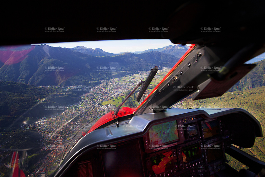 """Switzerland. Canton Ticino. Bellinzona. A Rega Agusta AW109 SP Grand """"Da Vinci"""" helicopter on its way to the nearest suitable hospital, Ospedale Regionale di Bellinzona e Valli, San Giovanni. All Rega helicopters carry a crew of three: a pilot, an emergency physician, and a paramedic who is also trained to assist the pilot for radio communication, navigation, terrain/object avoidance, and winch operations. The name Rega was created by combining letters from the name """"Swiss Air Rescue Guard"""" as it was written in German (Schweizerische Rettungsflugwacht), French (Garde Aérienne Suisse de Sauvetage), and Italian (Guardia Aerea Svizzera di Soccorso). Rega is a private, non-profit air rescue service that provides emergency medical assistance in Switzerland. Rega mainly assists with mountain rescues, though it will also operate in other terrains when needed, most notably during life-threatening emergencies. As a non-profit foundation, Rega does not receive financial assistance from any government. The AgustaWestland AW109 is a lightweight, twin-engine, helicopter built by the Italian manufacturer Leonardo S.p.A. (formerly AgustaWestland, Leonardo-Finmeccanica and Finmeccanica). Leonardo S.p.A is an Italian global high-tech company and one of the key players in aerospace. In close collaboration with the manufacturer, the Da Vinci has been specially designed to cater for Rega's particular requirements as regards carrying out operations in the mountains. It optimally fulfills the high demands made of it in terms of flying characteristics, emergency medical equipment and maintenance. Safety, performance and space have been increased, and maintenance and noise emissions reduced. 19.09.2017 © 2017 Didier Ruef"""