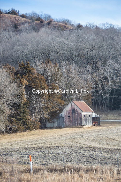 An old barn sits in a field on a farm in the country.