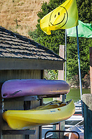 An unfurled Smiley Face flag flutters over two of the many boats available for rent at the Lake Chabot Marina.