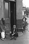 Middle aged working class couple  drinking and smoking sitting on the step of a Watneys Saloon public house, Notting Hill Gate  London 1975.