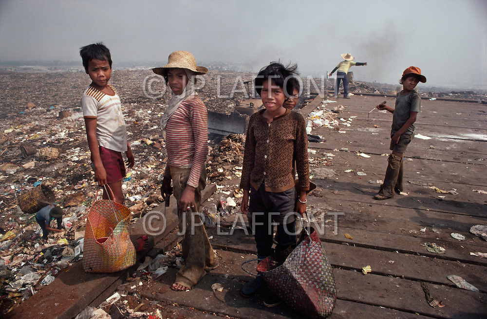 January 1979, Manila, Luzon Island, Philippines. Young children specialize in collecting various types of valuable trash from the Payatas garbage dump outside of Manila. Child labor as seen around the world between 1979 and 1980 - Photographer Jean Pierre Laffont, touched by the suffering of child workers, chronicled their plight in 12 countries over the course of one year.  Laffont was awarded The World Press Award and Madeline Ross Award among many others for his work.