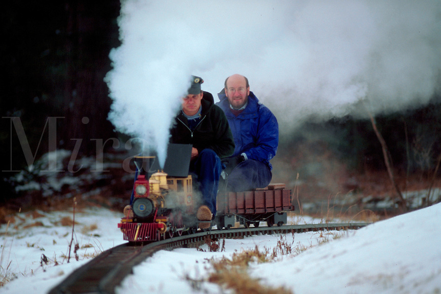 Model railroading - Men sit on a model train as it rides along tracks outdoors.
