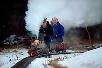 Model railroading - Men sit on a model train as it rides along tracks outdoors.