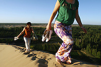 Tourists climbing sand dunes encroaching on farmland near the tourist attraction of Ming Sha Shan. Desertification is the process by which fertile land becomes desert, typically as a result of drought, deforestation, or inappropriate agriculture. Dunhuang, Gansu Province. China