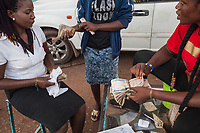 Nigeria. Enugu State. Enugu. Town center. Three Igbo women working at a petrol station count the money they earned while serving customers. The naira is the currency of Nigeria Enugu is the capital of Enugu State, located in southeastern Nigeria. 1.07.19 © 2019 Didier Ruef