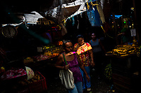 Afro-Colombian women walk around piles of fruits and vegetables while shopping in the market of Bazurto in Cartagena, Colombia, 6 December 2018. Far from the touristy places in the walled city, a colorful, vibrant labyrinth of Cartagena's biggest open-air market sprawls to the Caribbean seashore. Here, in the dark and narrow alleys, full of scrappy stalls selling fruit, vegetables and herbs, meat and raw fish, with smelly garbage on the floor and loud reggaeton music in the air, the African roots of Colombia are manifested.