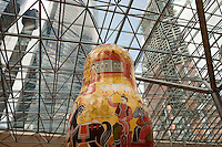 Moscow, Russia, 15/06/2011..A village scene on a giant Russian doll with new skyscrapers behind at an exhibition of of giant Russian matryoshki, or nesting dolls, in the newly-opened Afimall shopping centre. The dolls, designed by Boris Krasnov, are from 6 to 13 metres high, and each is decorated in a different style of traditional Russian folk art. This doll is in the Gorodetskaya style.
