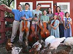 The Johnson siblings pose with their chickens, ducks, and string instruments in the backyard of their Littleton home.  Left to right:  Matthew, 21; Mark, 15; Timothy, 19; Nathan, 11; Laura, 17; Christina, 7; Joanna, 23; and Bethany, 9.  Lisa and Dale Johnson have 8 kids, ages 7-23 -- and all of them play string instruments.  We spend part of the day with them in their home in Littleton on Sept. 1, 2008.  (ELLEN JASKOL/ROCKY MOUNTAIN NEWS)
