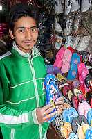 Nepal, Kathmandu.  Young Man Selling Flipflops.  Bindi or Tika between his Eyebrows.