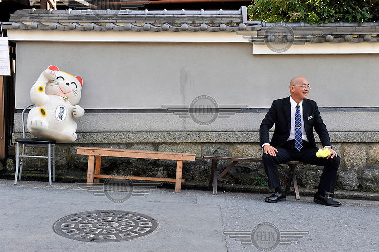 Taxi driver shares a bench with a stuffed toy as he waits for customers. /Felix Features