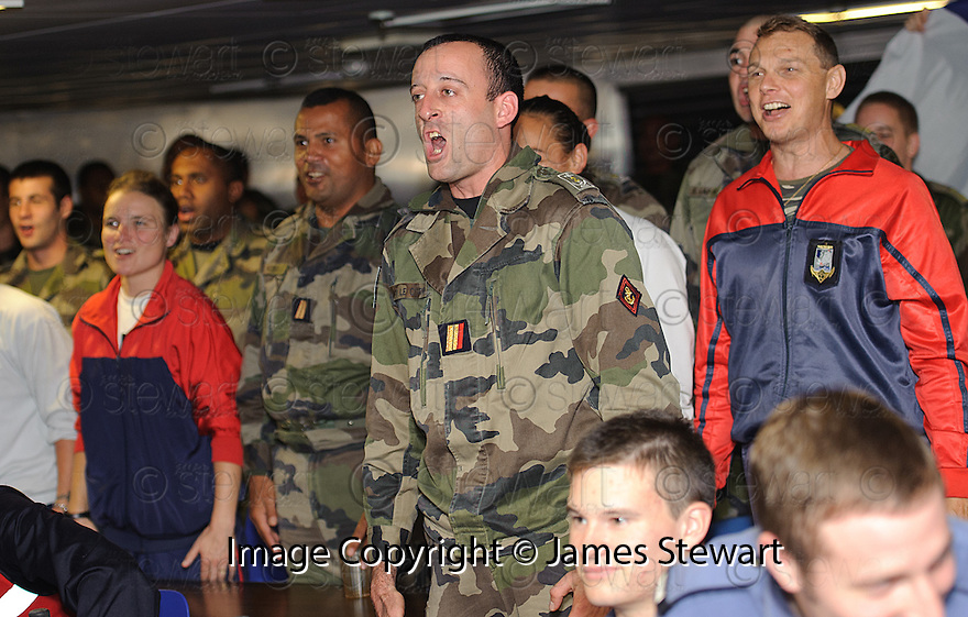 THE FRENCH SIGN THEIR NATIONAL ANTHEM NEAR THE END OF THE RUGBY WORLD CUP QUARTER FINAL BETWEEN FRANCE AND ENGLAND ON THE HMS BULWARK WHILST ON A BREAK FROM A JOINT EXERCISE IN LOCH EWE AND OFF THE SCOTTISH ATLANTIC COAST