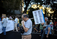 """A demonstrator holds a sign reading """"Enough morgage. Decent roof price"""" as he takes part in an anti-austerity protest in Madrid on September, 2012. Hundreds of Spaniards marched in Madrid to protest over hardships in a recession brought on by the financial crisis that they blame on banks and corrupt politicians. ©  Pedro ARMESTRE"""