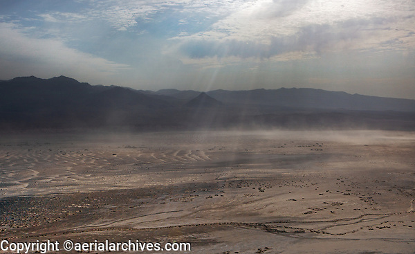 aerial photograph of dust being blown by winds in Death Valley National Park, northern Mojave Desert, California; dust storms develop the dunes in Death Valley.  The beginnings of dune formations are visible at left.