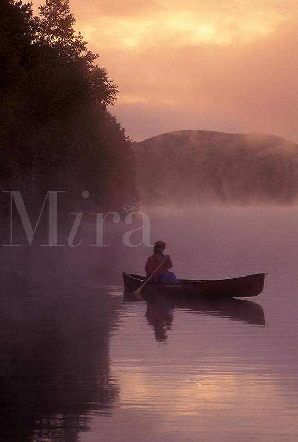 canoeing, canoe, sunrise, sunset, Vermont, VT, Woman paddling a canoe on Mollys Falls Pond at sunrise in the fog.