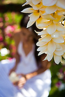 Beautiful Hawaiian woman making a fragrant plumeria lei on the lawn, with leis hanging in the foreground