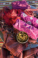Still life of brightly coloured and richly patterned pieces of fabric and a bowl of raisins