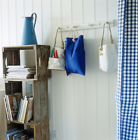 Blue and white bags hang from a coat rack mounted on a white tongue-and-groove clad wall with bookshelves fashioned out of old wine crates
