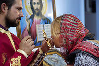 Italy. Lazio region. Guidonia. Father Sebastian is an orthodox priest and a romanian citizen. A romanian woman kisses the golden cross and the priest's hand at the end of the sunday mass. Icon of the Lord Jesus. Romanian immigration. Guidonia is a town and comune in the province of Rome. 02.10.2011 © 2011 Didier Ruef
