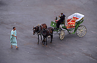 Man walking past a horse drawn cart in the town square of Djemaa el Fna, Marrakesh, Morocco.