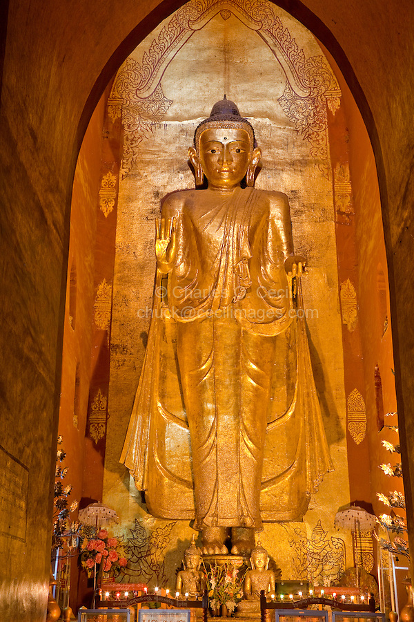 Myanmar, Burma. Bagan.  Buddha Statue, Ananda Temple, teak covered with gold leaf.  The Buddha's hands are in the abhaya mudra position, outstretched in the gesture of fearlessness.  This is the Buddha on the west side of the temple, an 18th-century replacement of the original.  The temple was built between 1090 and 1105.