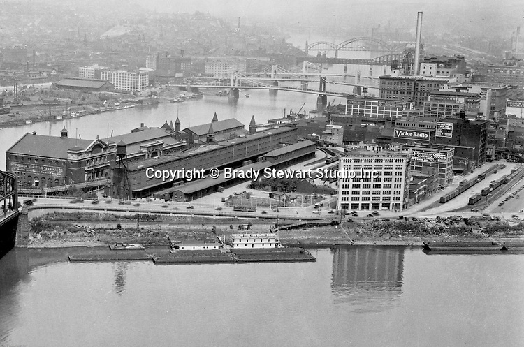Pittsburgh PA:  View of the Point Buildings and the new 7th & 9th Street bridges;  self-anchored suspension bridges spanning the Allegheny River.  Company signs are the city buildings include:  Victor Radio, Demmler & Schenck, Mackintosh Hemphill Company, Daugherty Company Canned Foods, Imperial Power Building, Union Electric Company, General Electric Wiring Systems, Pittsburgh Wharf and Terminal Company, Lent Traffic Company, Wheeling Steel Corporation Harbor, and the Alling & Cory Company
