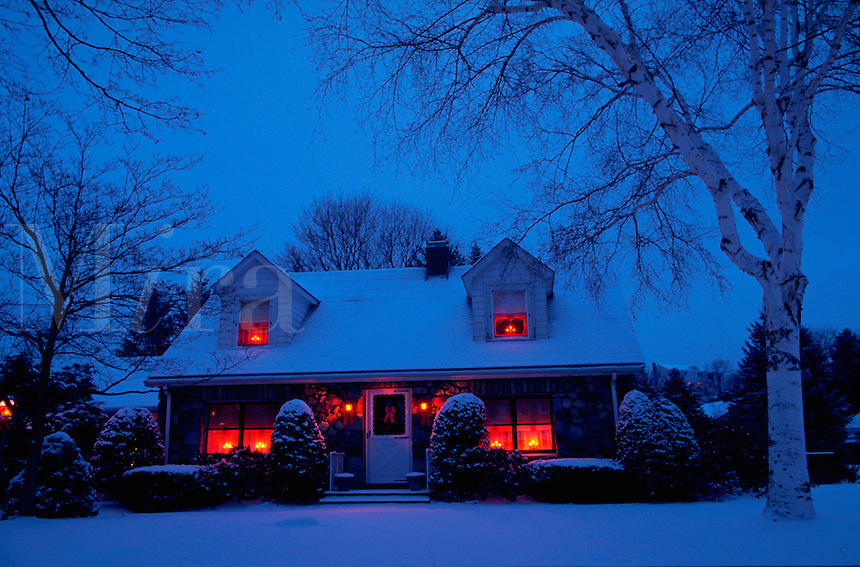 House at dusk with Christmas lights on in the windows.